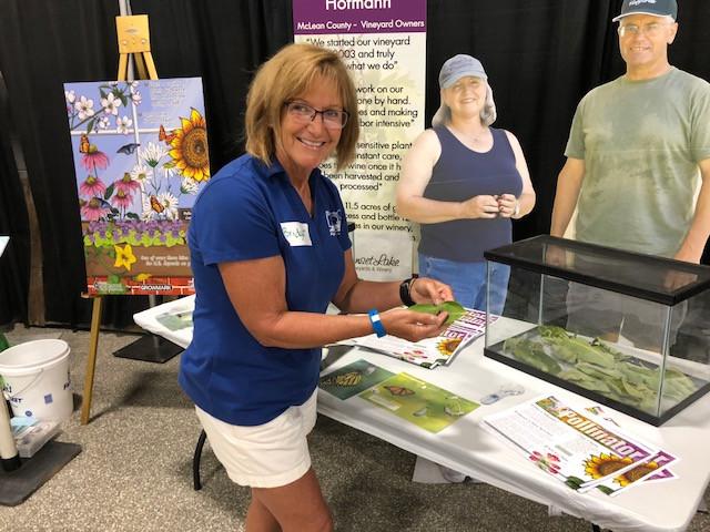 Bridget Caldwell poses next to the ag exhibit at this year's McLean County Fair / CIFN photo.