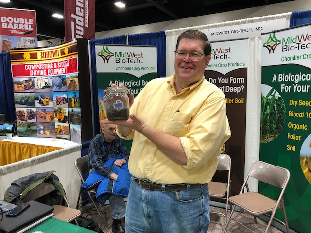 (Doug Miller with Midwest Bio-Tech displays a product at the Greater Peoria Farm Show on Tuesday / CIFN photo)