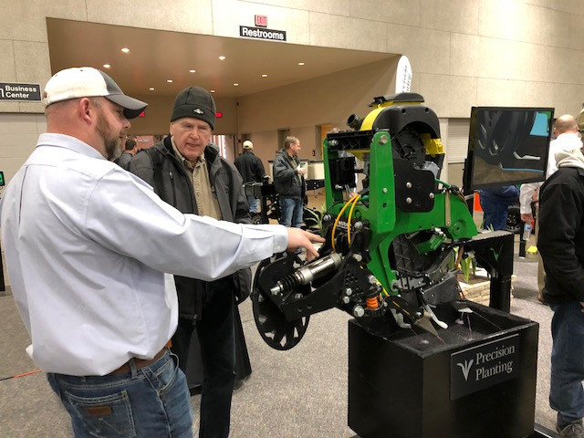 Dean Atkins (left) discusses planters with a visitor to the Greater Peoria Farm Show in November / CIFN photo.