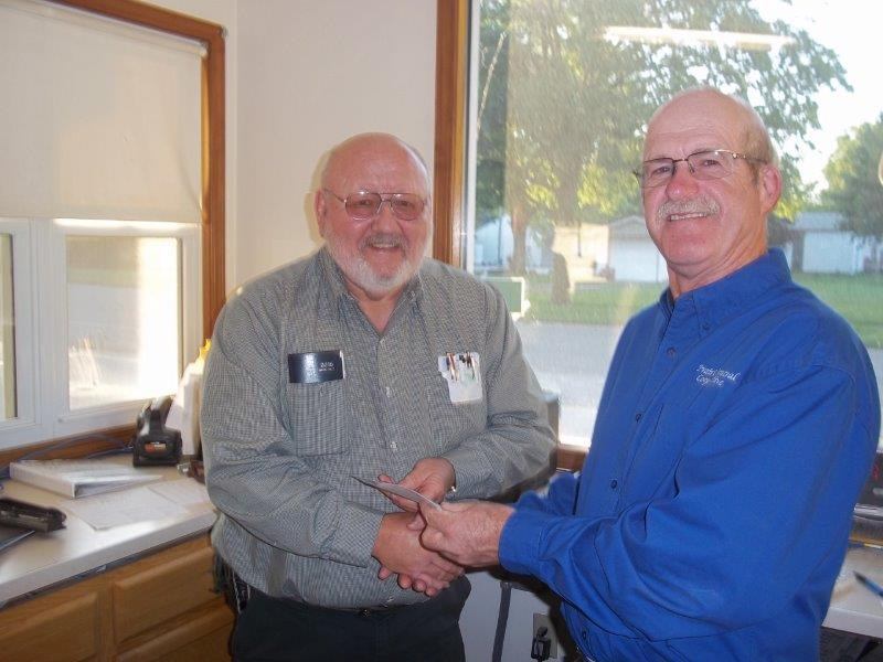 PC Coop's Gene Miller presents a check to Fairbury Fire Chief Leroy McPherson (photo provided by PC)