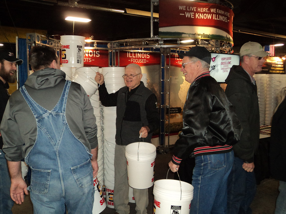 Farmers collect free buckets Wednesday at Midwest Ag Expo / CIFN photo