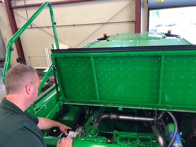 Kevin Yoder of KSR Equipment examines a combine in the shop / CIFN photo.