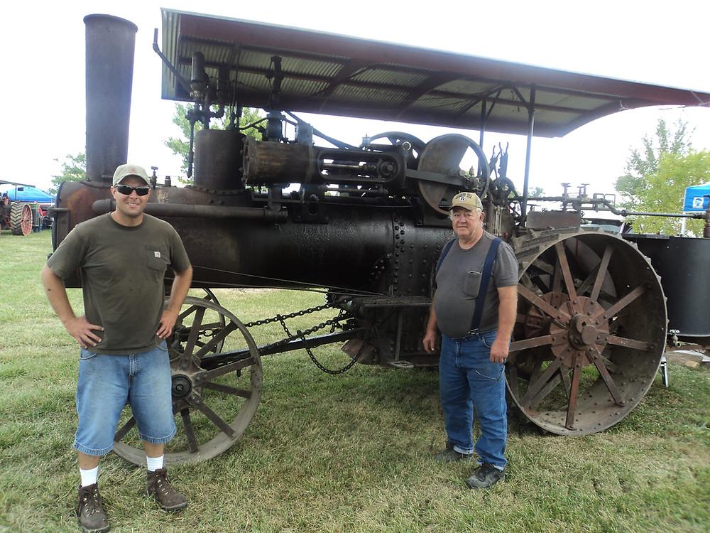 Chris (left) and Jim Erickson pose next to their steam engine at this week's Threshermen's Reunion near Pontiac / CIFN photo.