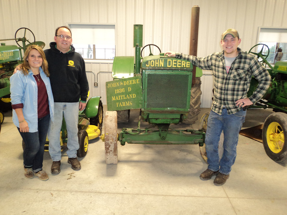 Justin Maitland (right) poses with his parents, John and Terri, at their farm west of Bloomington / CIFN photo.