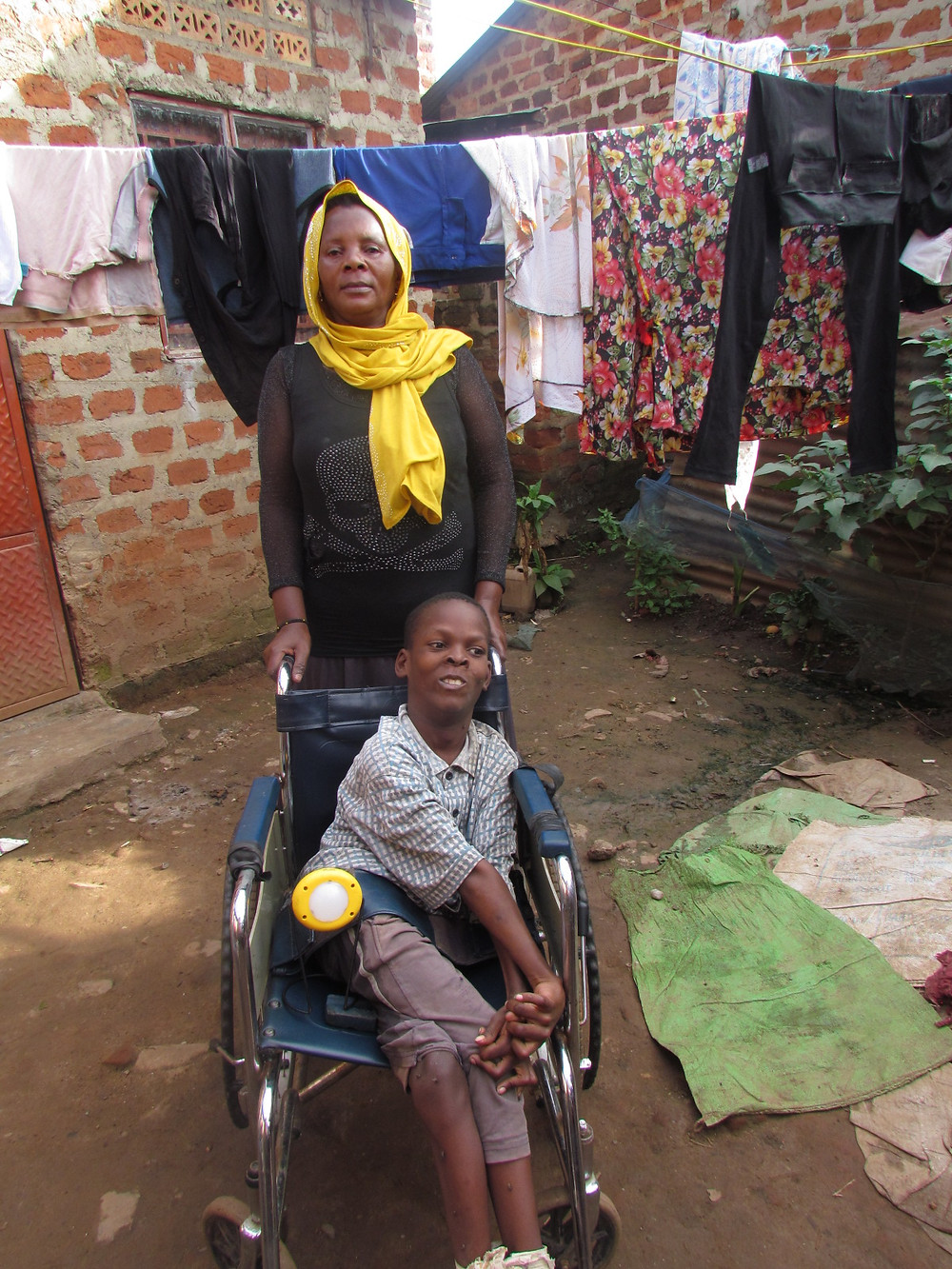 Abdul and his mother Tahia outside their home