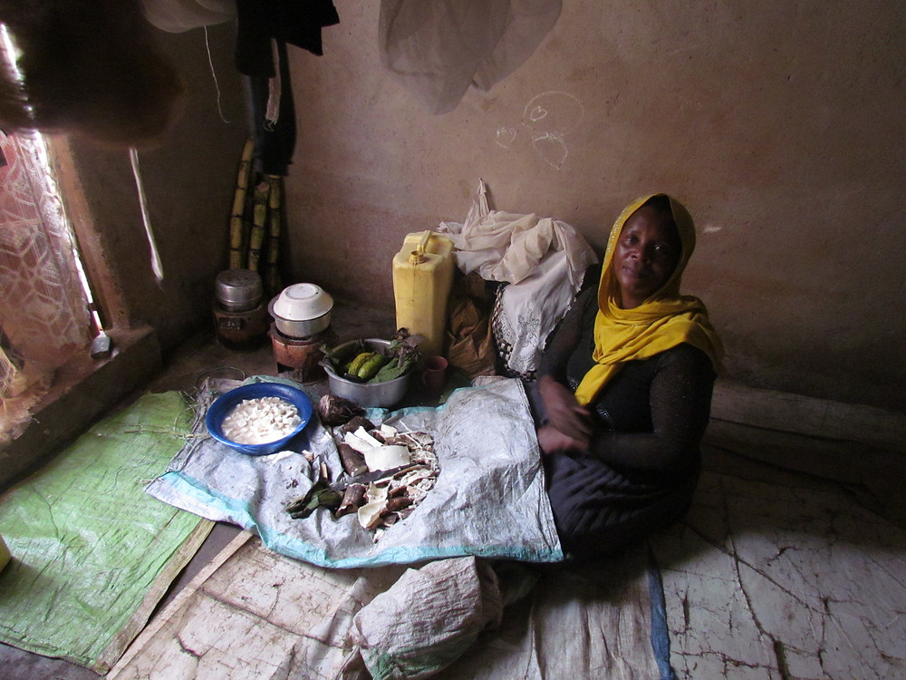 Tahia preparing food for her children inside their house