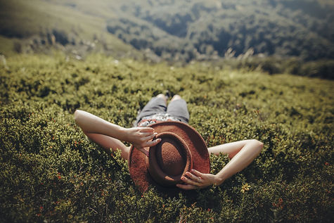 stylish traveler woman in hat lying on grass and relaxing in mountains. hipster girl on top of mount