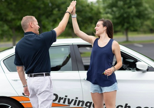 Todd and student driving giving high-five