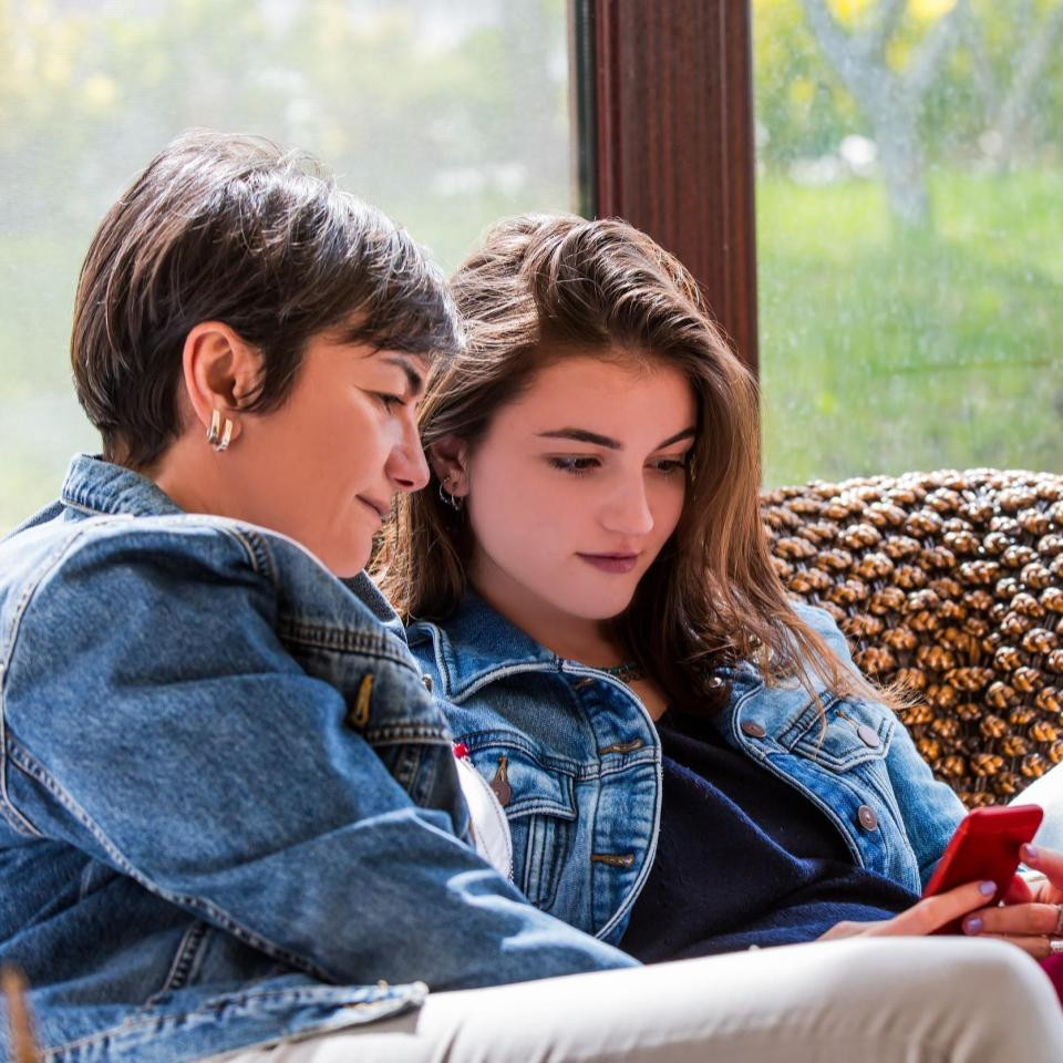 Mom and teen daughter sitting on couch looking at phone