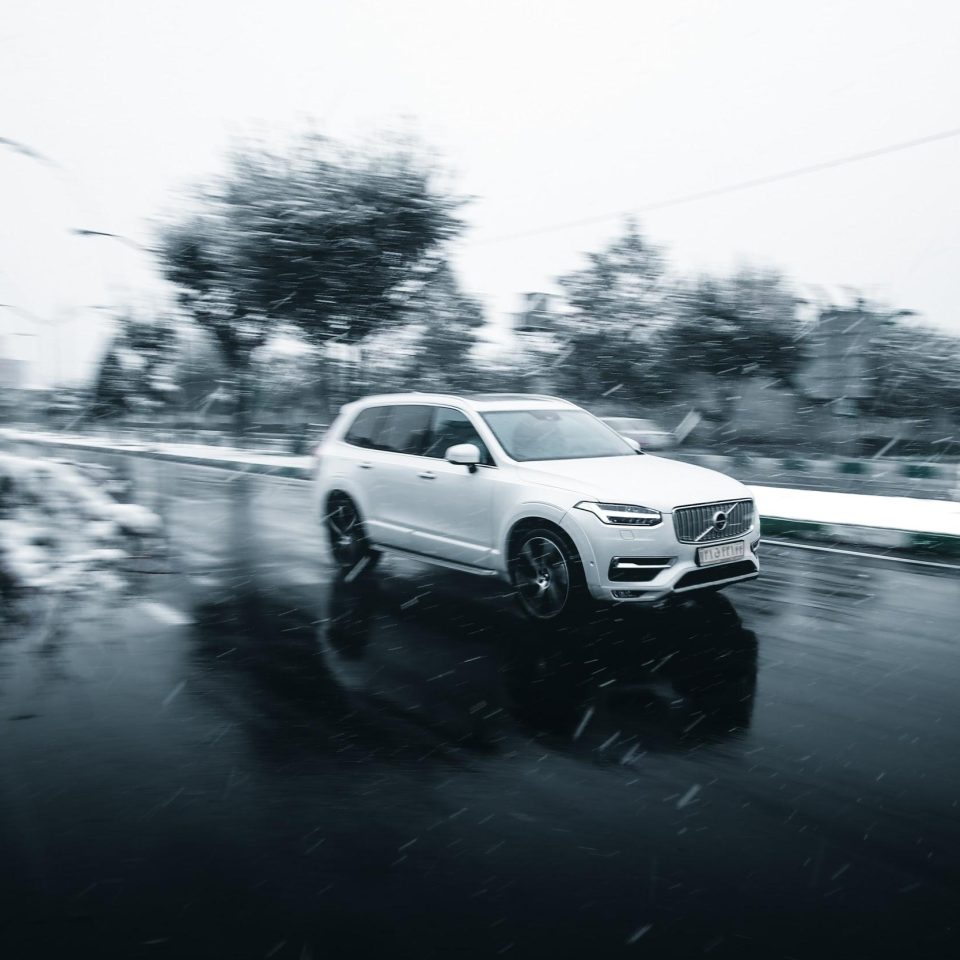 SUV driving on road while snowing