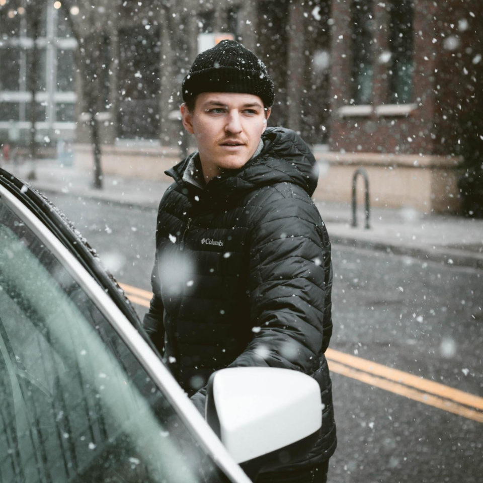 Man getting into car parked on road while it's snowing
