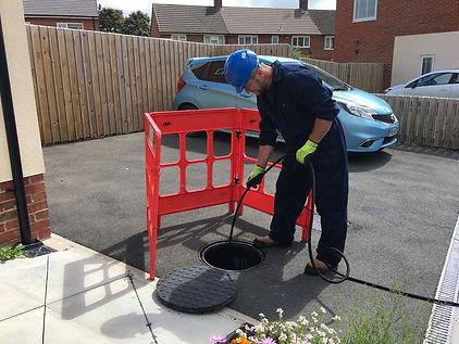 Man unblocking a blocked drain using high pressure jetting