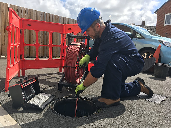 Man investigating drainage pipe to find the cause of a blocked drain