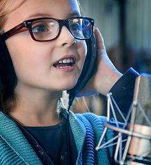 Kid singing in studio.Little girl singin