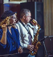 A singer and saxophonist in a restaurant
