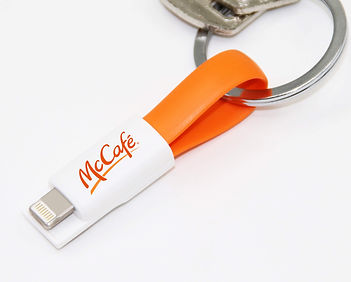 Promotional mini magnetic charger keyring cables for syncing data and charging phones, printed with company logos.