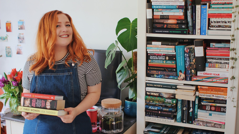 Sanne holding books with a bookshelf in the background