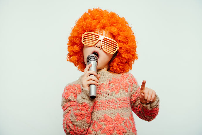 girl in a wig and sunglasses singing into a microphone.jpg a little girl wearing in a wig with a mic