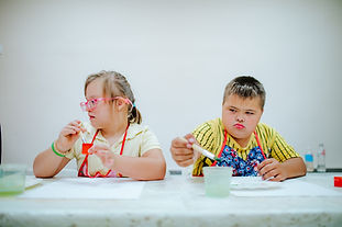 Boy and girl with Down syndrome draw at