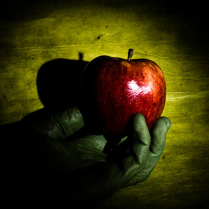 Green hand under Red Apple, on Green