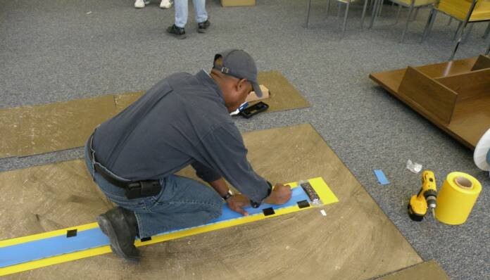 Qualified technician installing undercarpet power system
