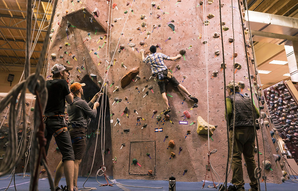 Customers climb rock wall during visit to REI store