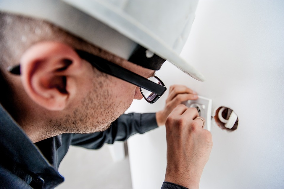 A qualified electrician working on a job in a store
