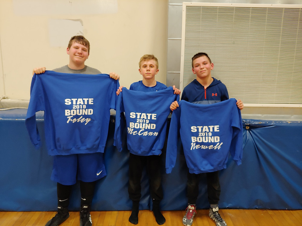 "Image of Middle School wrestlers holding up a blue sweatshirt that says ""State Bound 2019"""