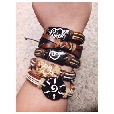 Four bracelets on a students arm.  Each bracelete contains a certain image.  Elephant, heart, turtle, and sun.