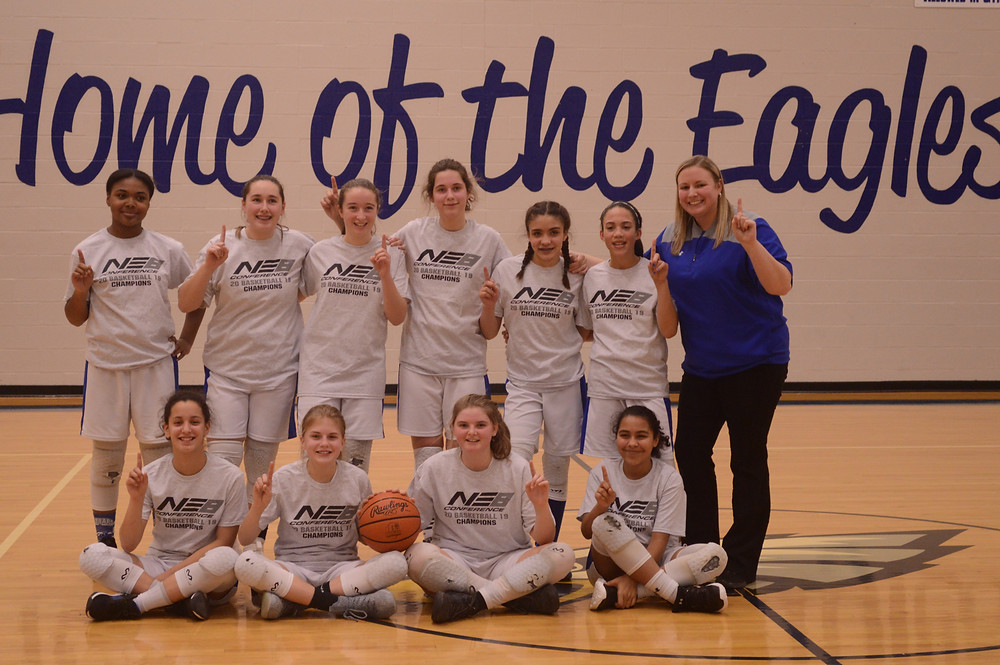 7th grade girls basketball team posing as champions of the North East 8 Conference