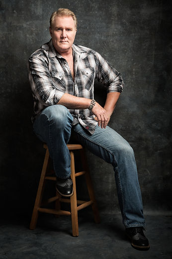Michael McGrady sitting on a wooden stool with jeans on and a black and white platt shirt
