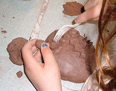 Kid making a clay sculpture