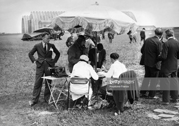 Organisateurs et journalistes, assis autour d'une table sur le terrain de l'aérodrome, préparent le départ de la course, à Orly, France en juin 1932. (Photo by KEYSTONE-FRANCE/Gamma-Rapho via Getty Images)