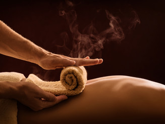 A professional therapist applies a hot towel on the back of a man. Hot towel compress. SPA