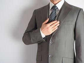 胸に手をあてるスーツの人