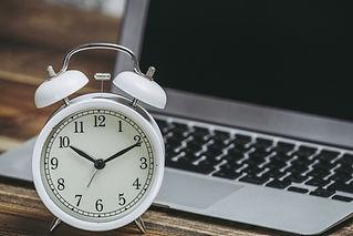 白いアナログの置時計とパソコン