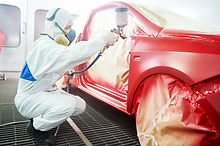 auto mechanic worker painting a red car in a paint chamber during repair work.jpg