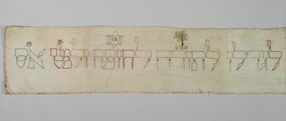 """detail of a Torah binder showing the phrase, in Hebrew, """"to grow up to Torah, Chuppah and Good Deeds"""" embroidered on it"""