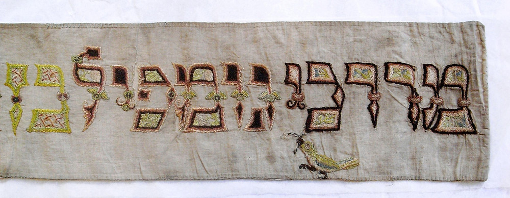 Detail from a German Torah binder, showing gaily embroidered text and a little embroidered bird