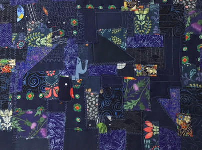 Sample of fabric collage using small pieces of navy fabric, held down by free motion and decorative machine stitching