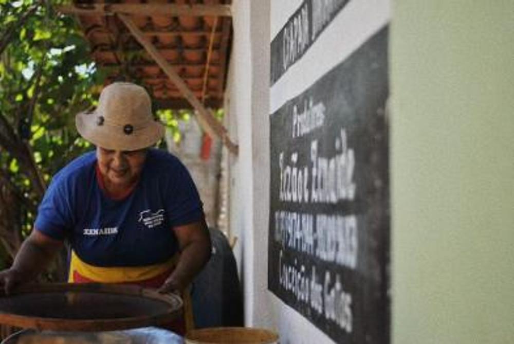Ensaio fotográfico de mulher, produtora de café orgânico no Vale do Capão - Chapada Diamantina (BA), sorrindo a luz do dia em sua loja simples, mas com lições de marketing e experiência de consumo