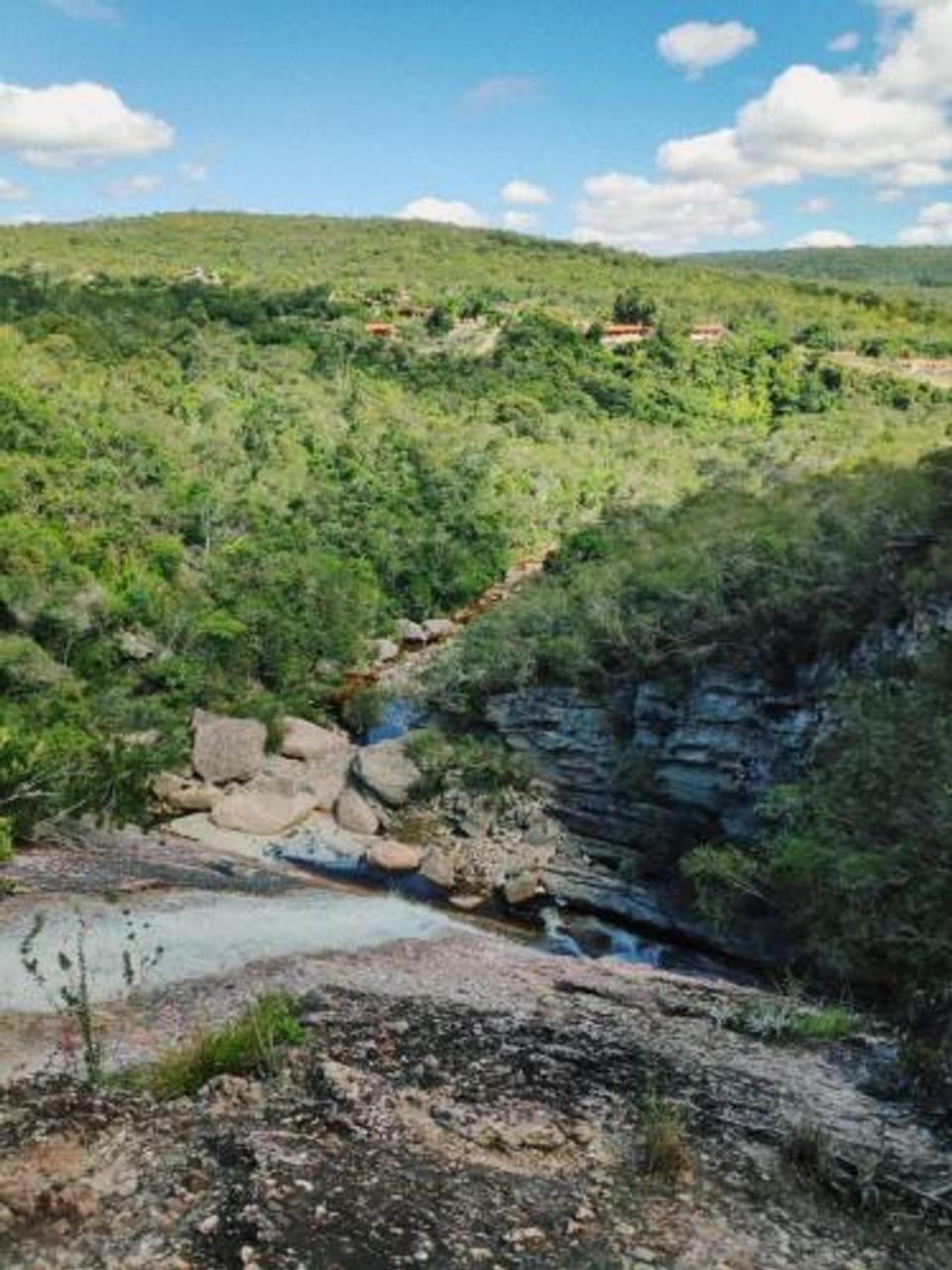 Paisagem da trilha Cachoeira da Conceição dos Gatos no Vale do Capão - Chapada Diamantina (BA). Vista do alto de uma cascata: pedras, topos de árvore e céu azul.