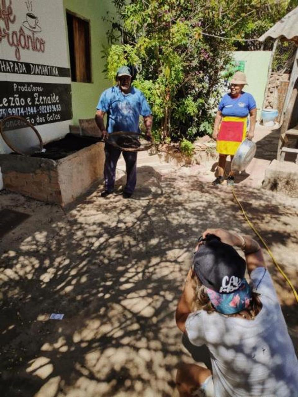 Ensaio fotográfico de casal, produtores de café orgânico no Vale do Capão - Chapada Diamantina (BA), sorrindo a luz do dia em sua loja simples, mas com lições de marketing e experiência de consumo