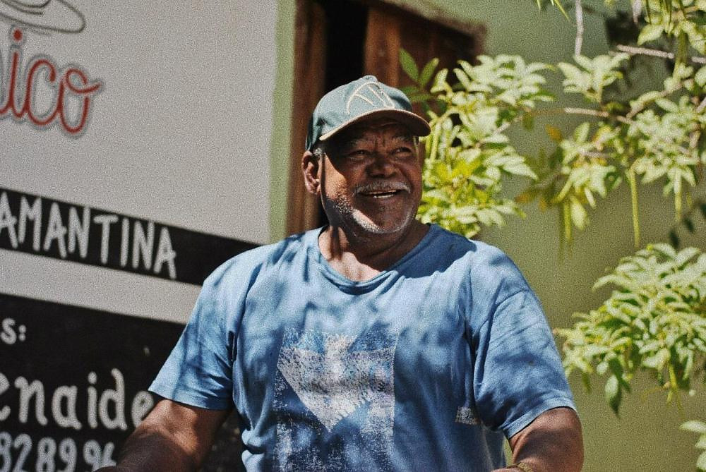Ensaio fotográfico de homem, produtor de café orgânico no Vale do Capão - Chapada Diamantina (BA), sorrindo a luz do dia em sua loja simples, mas com lições de marketing e experiência de consumo