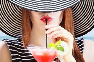 Dame au chapeau qui boit un cocktail ros