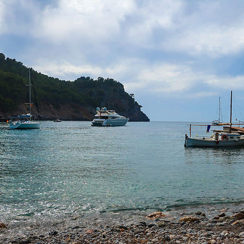 beach of cala tunes with boats on a summer day