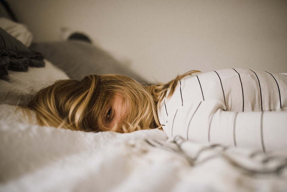 A woman lying in bed with blond hair over her face, white shirt with thin black stripes, white blanket and wall
