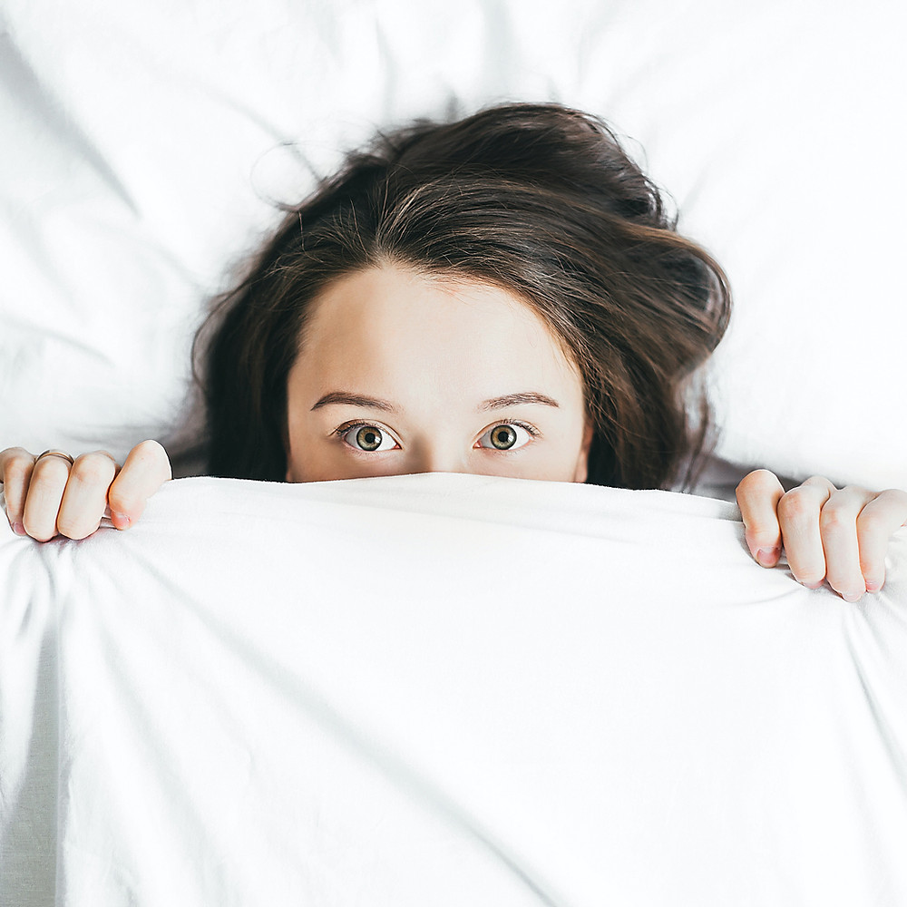A woman pulling a white sheet up to her eyes lying in bed. Kristi Ryan Holistic Nutrition