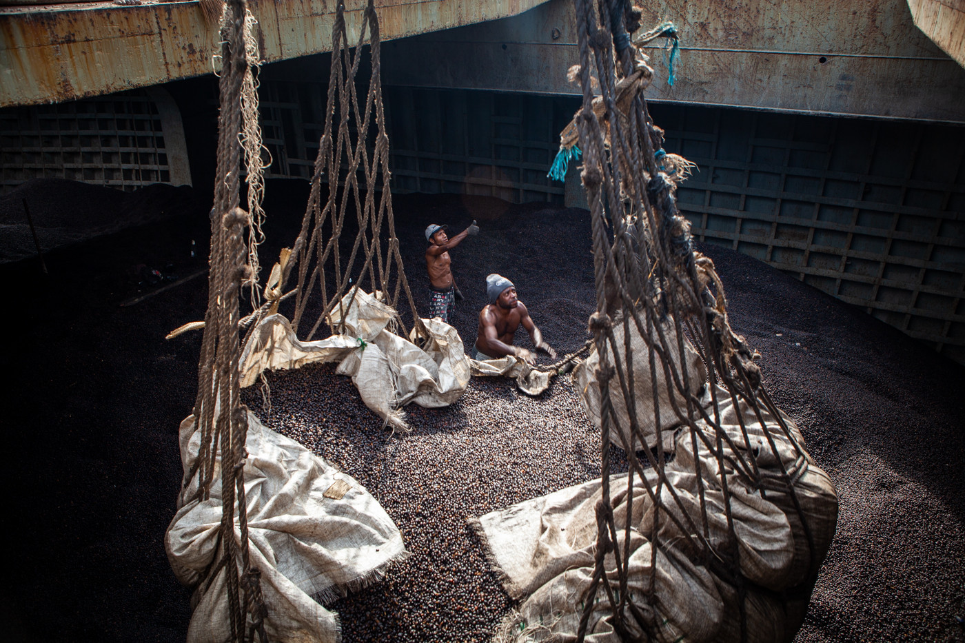 In all-consuming heat and treacherous conditions, two workers load thousands of pounds of palm nuts (the raw form of palm oil) into the multi-ton ship hull.  Sans safety gear, they are covered in pesticide residue and the greasy (itchy) oil that coats the palm nuts.