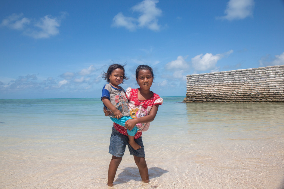 035_34Island children who moved to Tarawa, Kiribati so their dad can build this sea wall (behind) for a new building_photo credit Sarah Fretwell.jpg